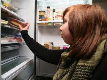 Una joven coge una hamburguesa de la nevera