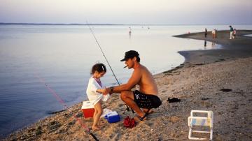 Un hombre pesca con su hija