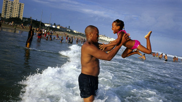 Un padre juega con su hija en la playa