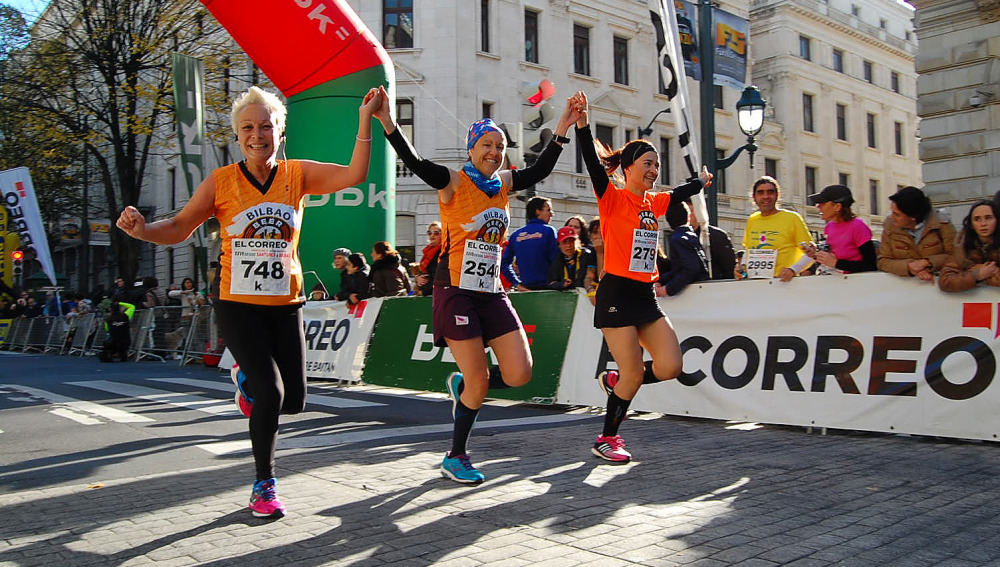 Un grupo de corredoras sonríe antes de cruzar la línea de meta