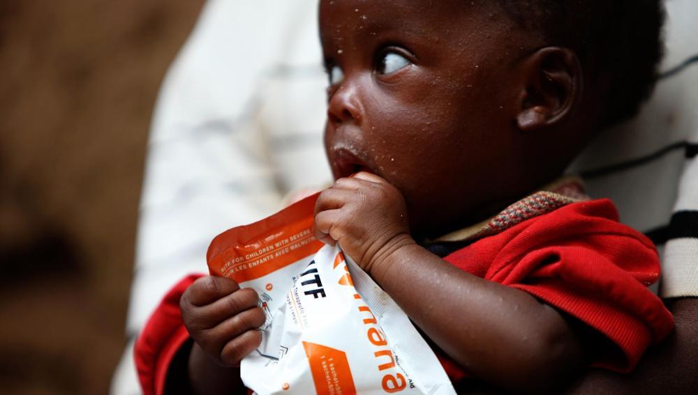 Un niño de Ruanda con un paquete de comida nutricional