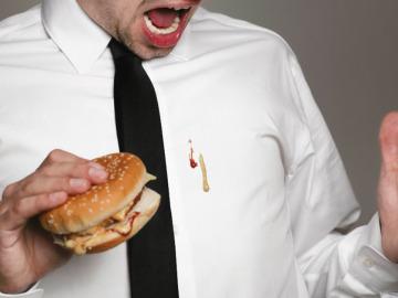 Un hombre se mancha la camisa comiendo una hamburguesa
