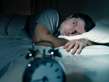 Imagen de archivo de un hombre tratando de dormir.