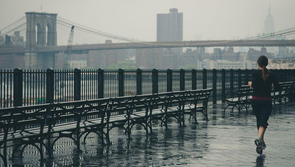 Una chica corre en un día de lluvia