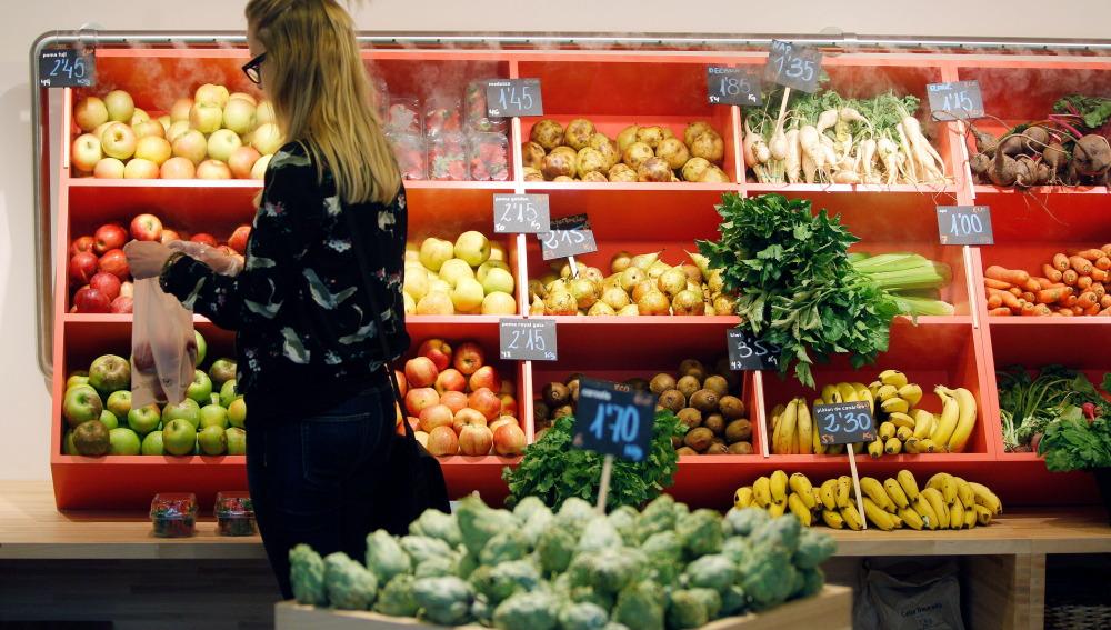 Una mujer hace la compra en la sección de frutas y verduras