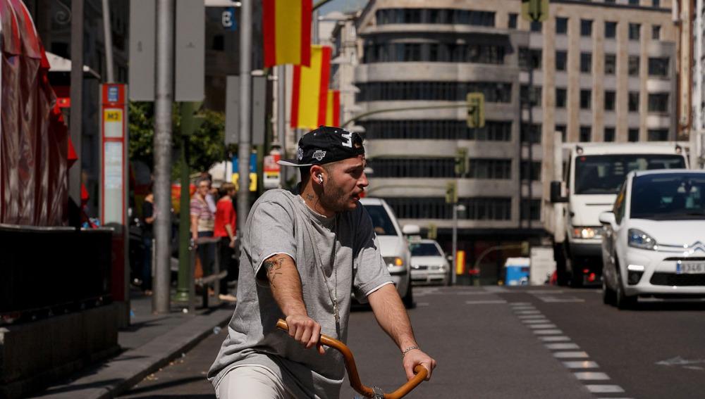 Un ciudadano conduce su bici por la Gran Vía