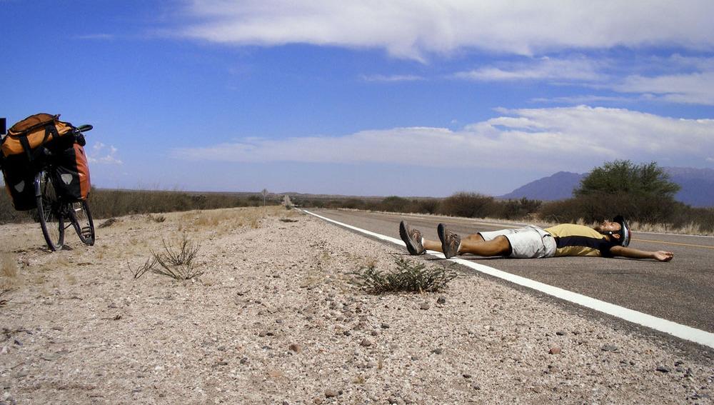 Ciclista tumbado en la carretera
