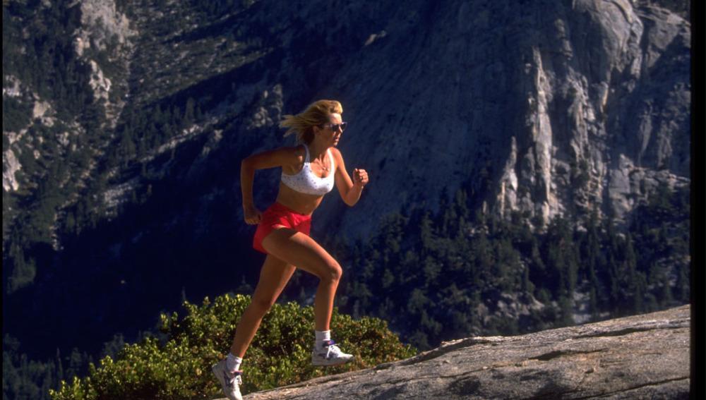 Mujer corriendo por montaña