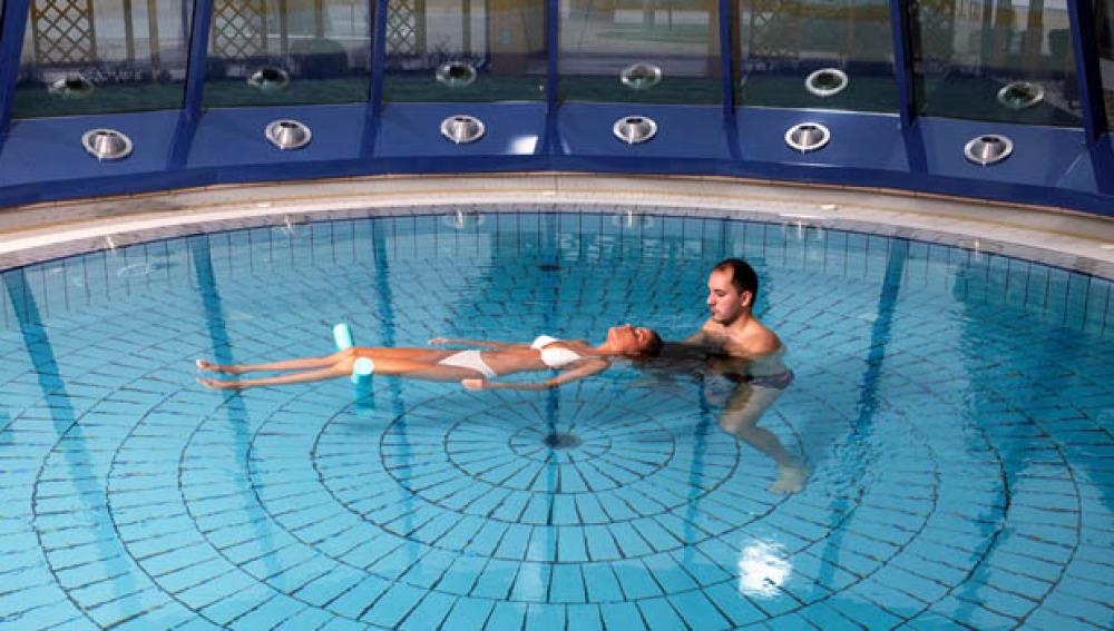 Una mujer practica Watsu en la piscina