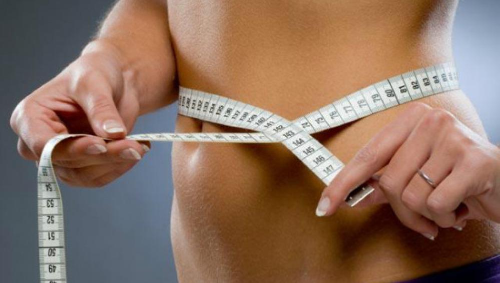 Una mujer se mide la cintura