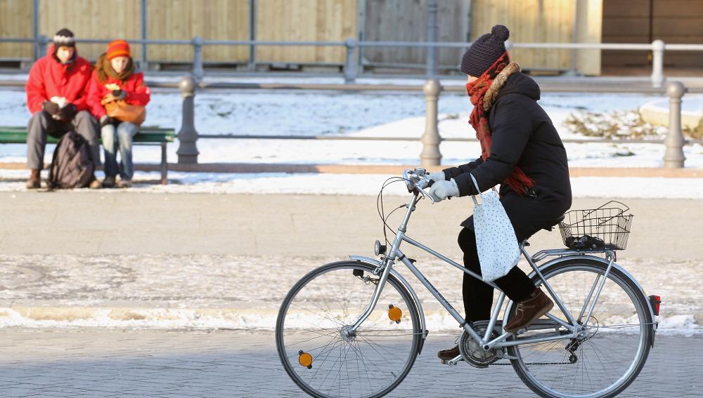 Una ciclista en bici con mucho frío