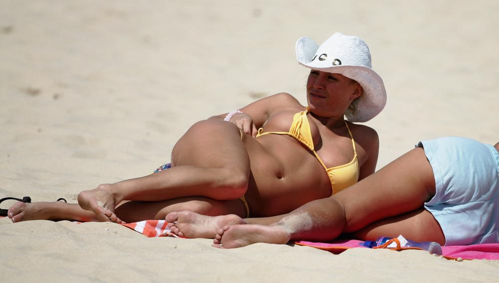 Una mujer toma el sol en la playa
