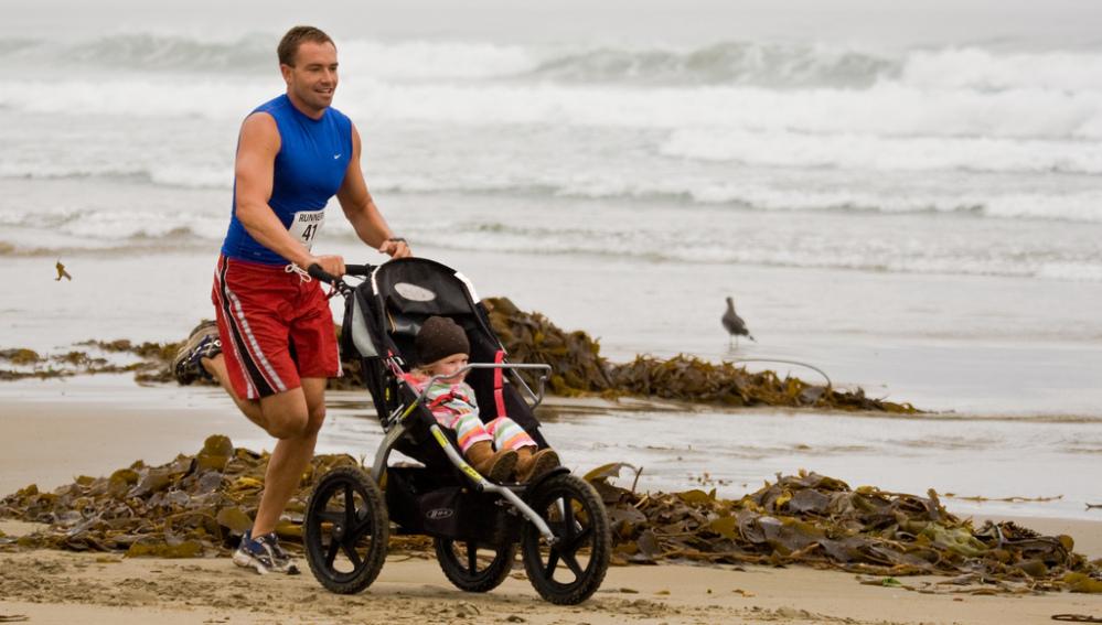 Un hombre corre en la playa con un bebé