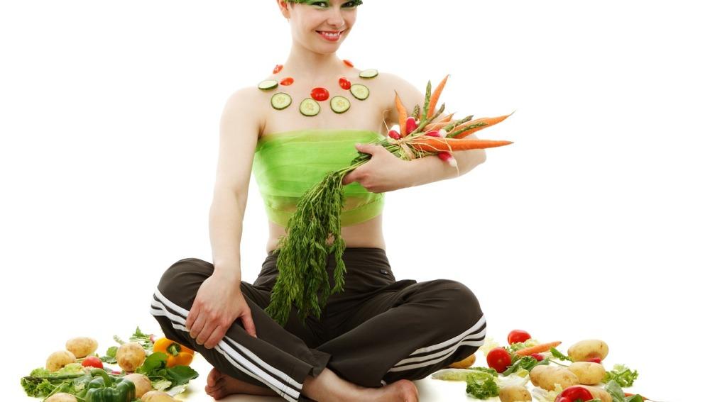 Una persona rodeada de verduras