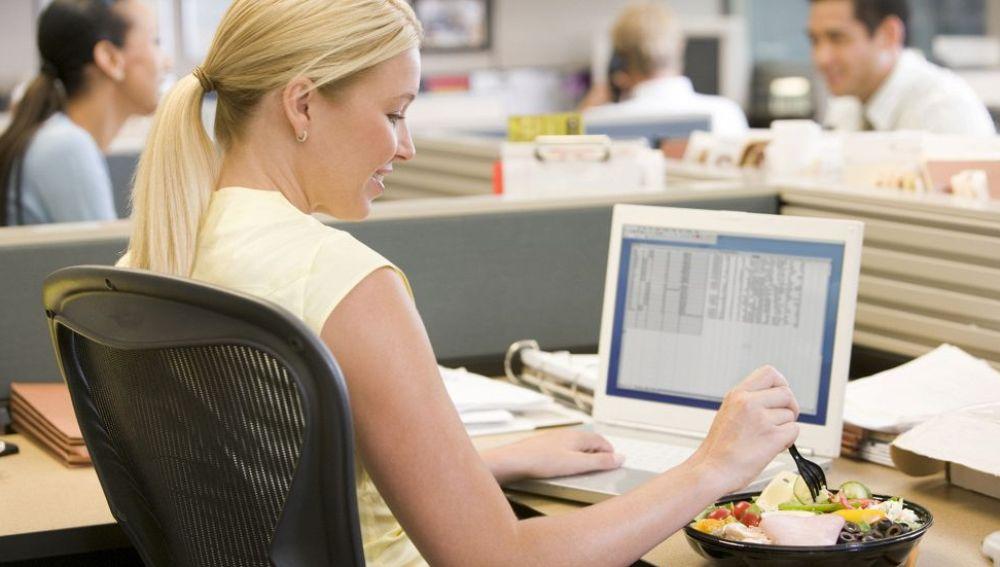 Una mujer come en el trabajo