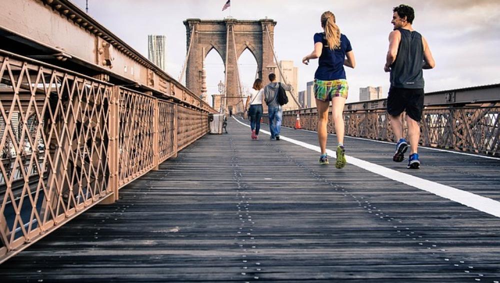 Una pareja corre sobre un puente