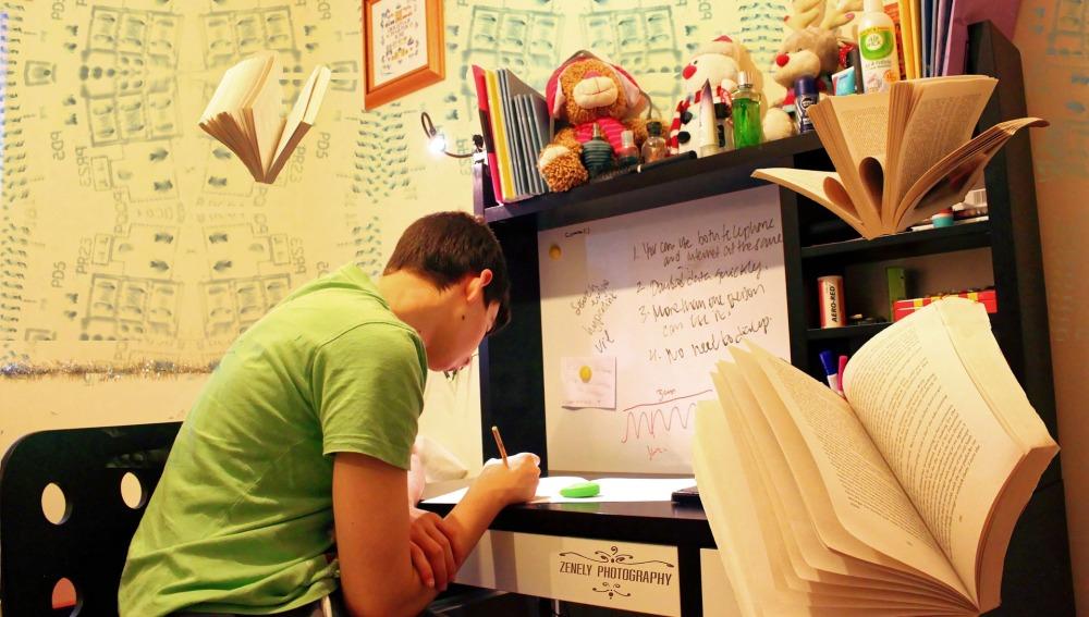 Un chico estudiando en su habitación