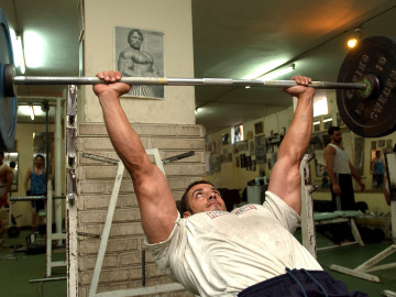 Un hombre trabaja con pesas en el gimnasio