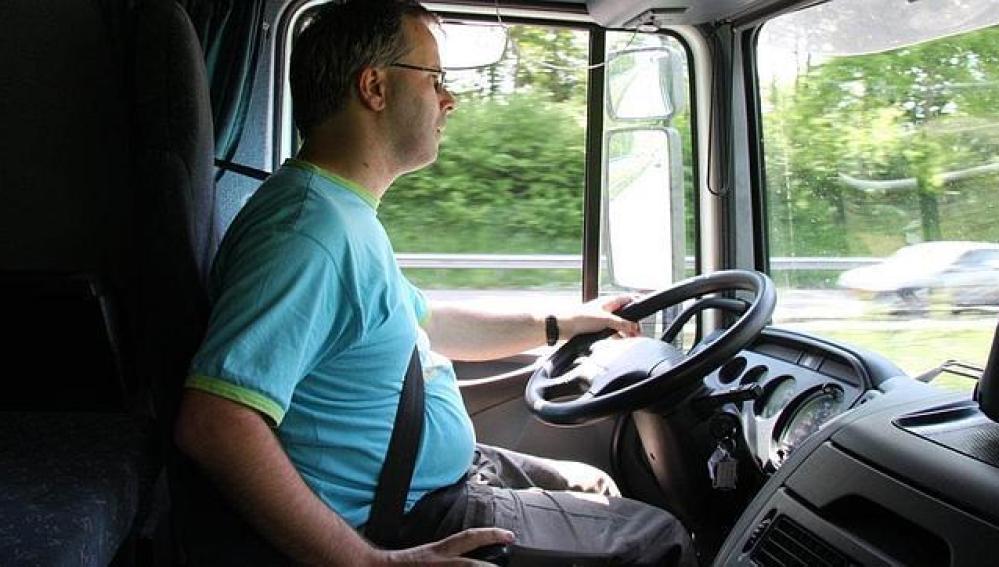 Un camionero con barriga conduciendo