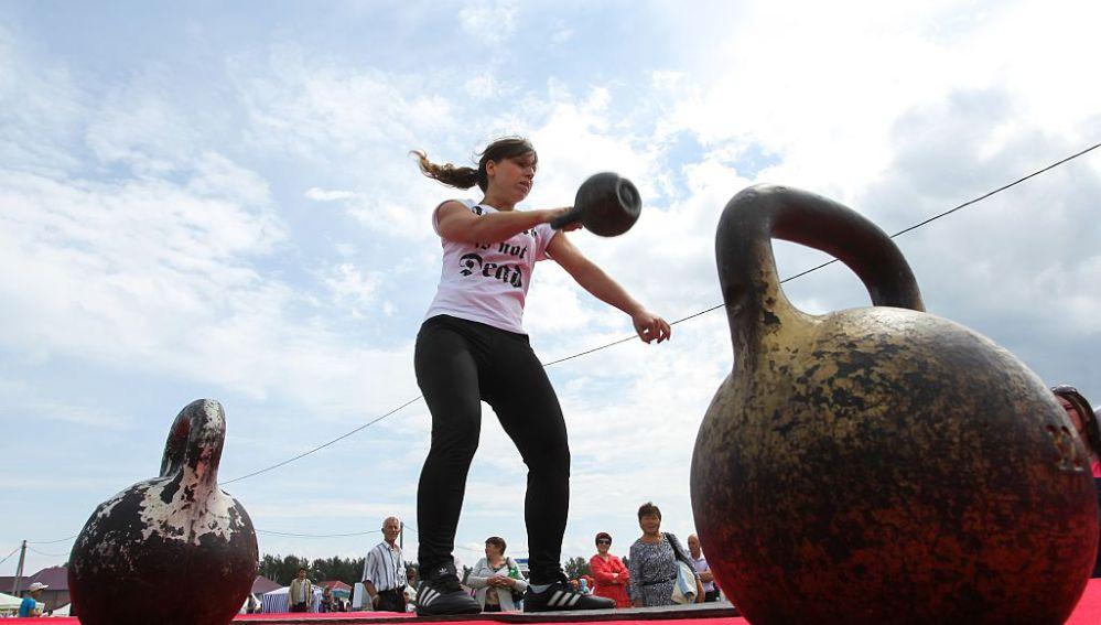 Una mujer levanta pesas rusas