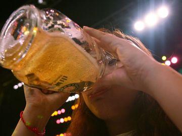 Una mujer bebe una cerveza