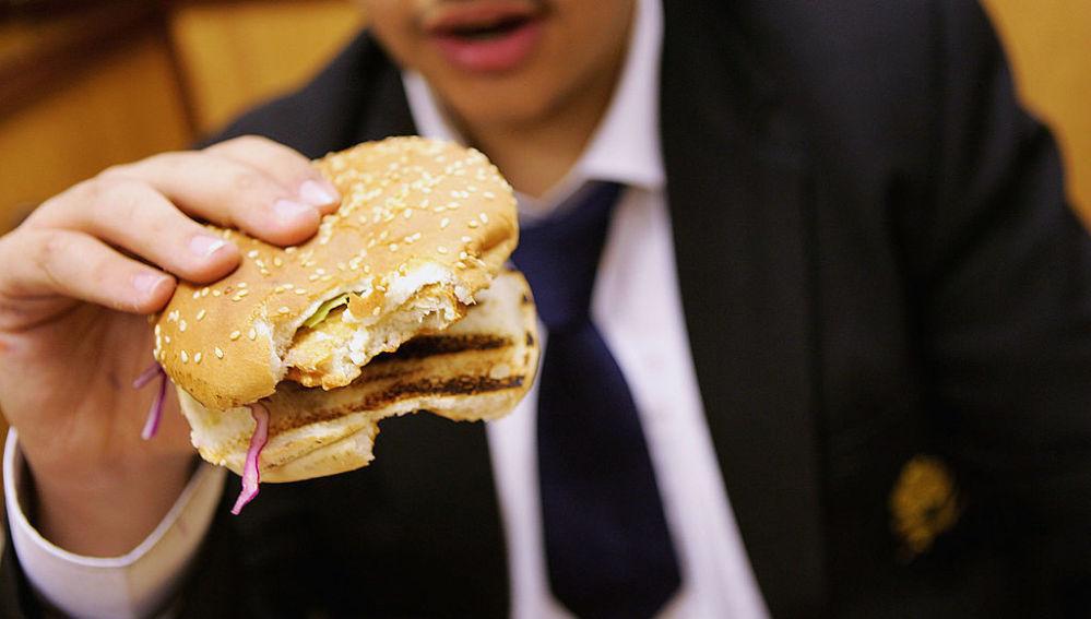 Un colegial come una hamburguesa para almorzar