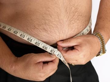 Un hombre se mide la barriga