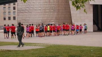 Un grupo de runners atiende a las instrucciones de un entrenador personal
